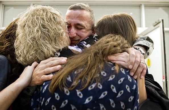 Major Tom Walton is hugged by his family