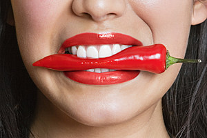 Woman biting red pepper